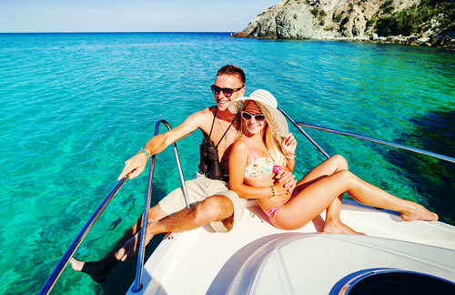 Couple Smiling on a Yacht over Clear, Blue-Green Water